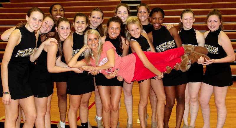 The STA varsity dance team girls hold up their coach and Kansas City Chief's Cheerleader Christina Monaco.