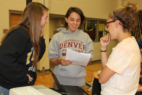 "Seniors Liz Wiens, left, Melissa Lane and Lucy Edmonds prepare for a presentation about teen depression and suicide April 27. The three girls organized the ""Out of the Darkness"" event. Photo by Allison Fitts"