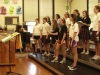 Choir teacher Michelle McIntire yells encouragements as the choir rehearses a song during their last after school rehearsal. The girls had been staying after school every day possible to prepare for the WorldStrides Heritage Festival in Chicago April 14.By Emily Coble