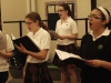 "Freshman Annie Huber, from left, freshman Madalyn Schulte, freshman Monica Stanley, freshman Alexia Arrieta, and freshman Liz Mitchell practice ""Now I Become Myself"" during the beginning of rehearsal April 4. The choir split into alto, mezzo, and soprano groups. By Emily Coble"