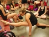 Freshman Gretchen Schloegel stretches in front of freshman Alex Amey, from left, junior Sara Meurer, and junior Erin Rasmussen in the main locker room during dance team tryouts on April 3. Schloegel and other dancers continually stretched while waiting for their turn in the tryout rotation. By Eden Kreighbaum