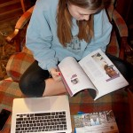 Senior Emma Rebein flips through an informational pamphlet about one of her prospective UK colleges in her living room on Tuesday, Dec. 11. Rebein has been researching foreign universities for months, trying to decide if they are right for her. She plans to visit potential UK schools in mid-January with her father.