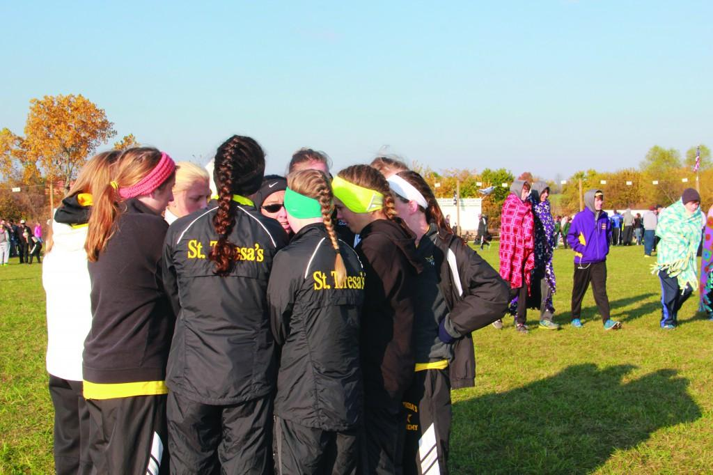 The varsity cross country team huddles together with head coach Karen Moran at the Class 4, Sectional 4 meet Nov. 9. photo by Mary Hilliard